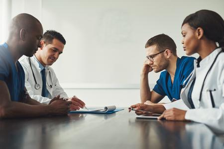 의료 직원 회의. 서로의 앞에 테이블에 앉아 흰색 코트와 파란색 유니폼에 젊은 사람들의 그룹입니다. 복사 공간이 낮은 각도 측면보기
