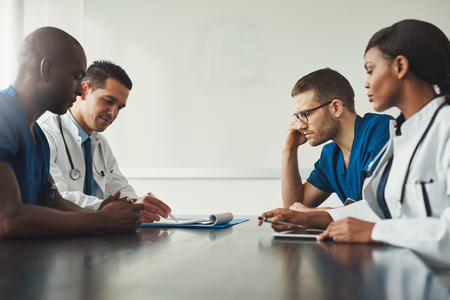 Medical staff meeting. Group of young people in white coats and blue uniform sitting at table in front of each other. Low angle side view with copy space Stock Photo