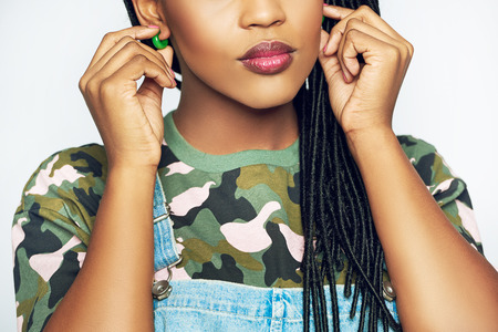 Young black African american woman with long braided hair adjusting her green earrings in her pierced ears with her hands, close up cropped view