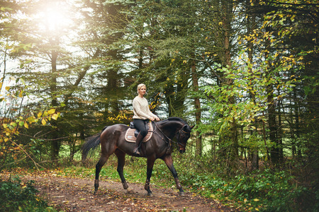 Full size portrait of a woman riding a horse in the park Stock Photo