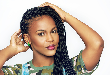 Gorgeous graceful young black African american woman with long braided hair raising her hands to her head as she looks at the camera with a quiet smile