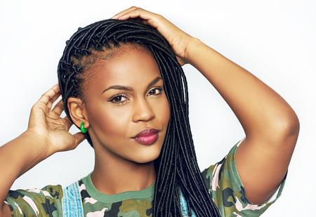 Herrliche anmutige junge schwarze African American Frau mit langen geflochtenen Haaren, die ihre Hände an den Kopf zu heben, als sie in der Kamera mit einem ruhigen Lächeln schaut