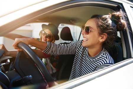 Two fun young women in sunglasses driving in a car in town laughing and smiling as they socialise together, view through open side window