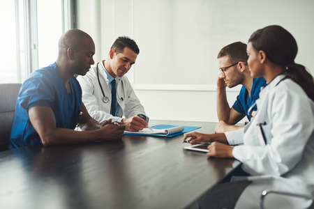 Multiracial medical team having a meeting with doctors in white lab coats and surgical scrubs seated at a table discussing a patients records