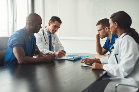 Multiraciale medisch team met een bijeenkomst met artsen in witte laboratoriumjassen en chirurgische scrubs zittend aan een tafel over een patiënten-records Stockfoto - 75315633