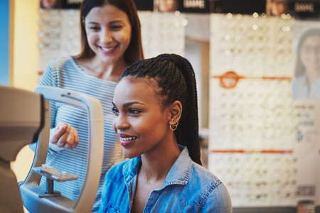 testing vision: Smiling young black woman sitting at a machine in an optical shop is ready to take eye exam Stock Photo