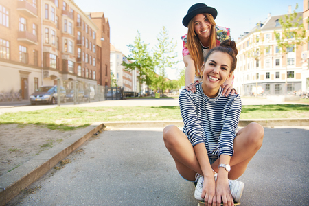 Cute gorgeous vivacious young woman sitting on a skateboard with a trendy young friend leaning on her shoulders grinning at the camera in an urban street