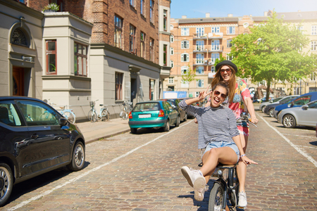 Friend riding on bike with teen girl outside going in wrong direction on brick covered street in city