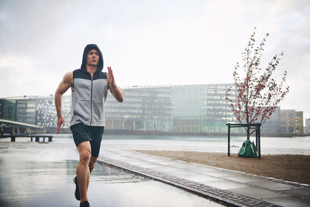 Athletic man in sleeveless hoodie and shirts jogging in rainy day outdoors in city park, with modern buildings in background and grey moody sky above