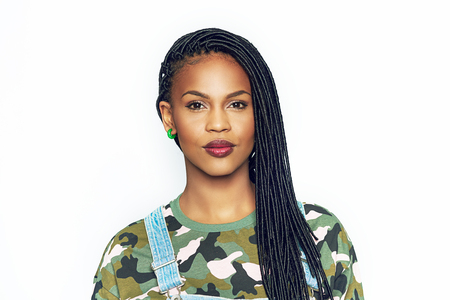 Pretty black African american woman with braided hair and makeup pouting her red lips at the camera as she poses with her long hair over one shoulder isolated on white Standard-Bild