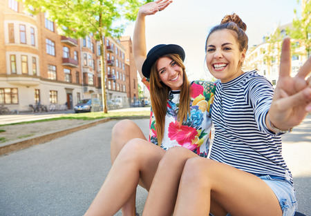 Cute friendly girls waving at the camera with beaming smiles as they sit on a skateboard in an urban street Stock Photo