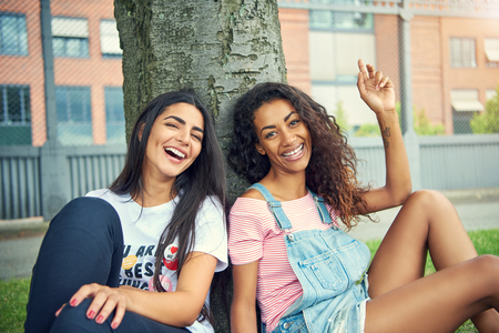 Two laughing friends sitting beside each other with a large tree trunk and urban apartment building behind them Stock Photo