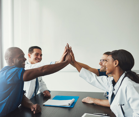 Group of young medical personal people connecting their hands in team spirit high five over table, sitting in front of each other. Side view with copy space 免版税图像