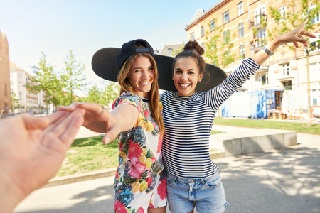 Smiling trendy woman standing arm in arm with her friend posing with their skateboard reaching out her hand to touch her boyfriend