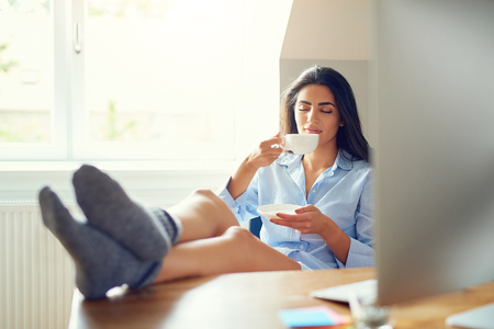 energising: Calm woman in bare legs and gray socks with feet on desk sipping coffee from white cup in home office Stock Photo
