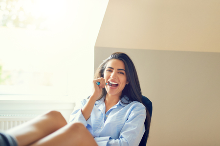 Laughing beautiful young woman using her toothbrush while seated at home in home office Stock Photo