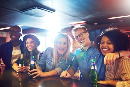 Horizontal? Tiro de feliz grupo de amigos en el bar bebiendo la cerveza y mirando a la cámara.