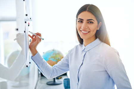 Gorgeous single young female business woman or instructor holding an erasable marker in hand at white board