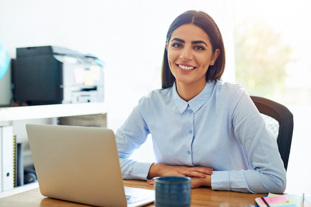Smiling friendly young businesswoman entrepreneur working from a home office sitting at a laptop computer looking at the camera with a charming smile