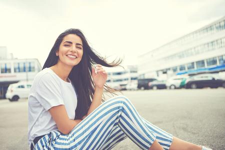 風吹き髪と縞パンツの駐車場で座ったままカメラに向かって笑顔の女性 写真素材