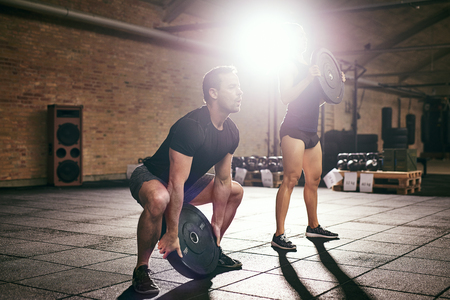 Sportive man and woman doing exercise with weight discs from squat in light spacious gym.