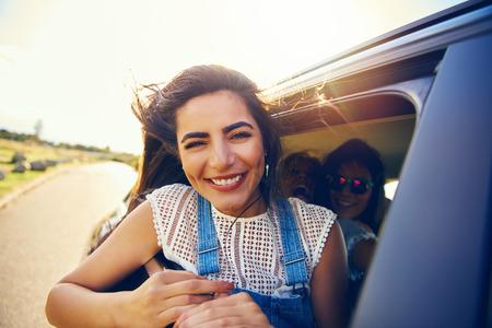 iluminado a contraluz: Mujer joven atractiva con una radiante sonrisa asomada a una ventana de coche cuando va de viaje de vacaciones de verano, vista de cerca Foto de archivo