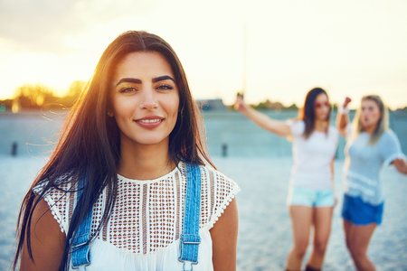 introspective: Smiling pretty woman in long brown hair and blue jean overalls on beach with two girlfriends Stock Photo