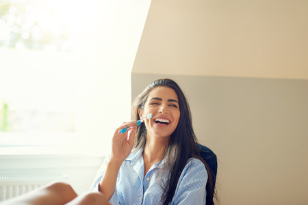 Laughing beautiful young woman in long hair and blue long sleeve shirt holding toothbrush at home