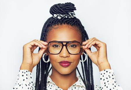 negras africanas: Retrato de joven mujer de moda negro tratando de gafas, fondo blanco Foto de archivo