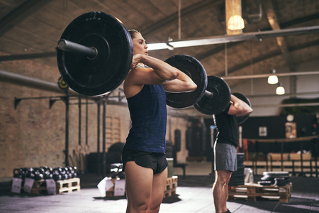 Fit people holding barbells on their shoulders while exercising. Horizontal indoors shot Stock Photo