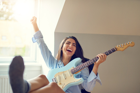 Beautiful single singing woman playing guitar with raised arm and feet on table in room with bright window