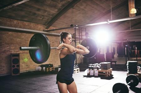 Joven y fuerte barra de elevación de la mujer en el gimnasio. horizontal tiro