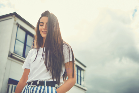 Woman wearing striped pants puts hand in pocket and smiles as hair hangs in face
