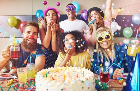 大きなケーキとフォア グラウンドでテーブルの上のドリンク パーティーを祝う陽気な友人のグループを取り巻く吹流し