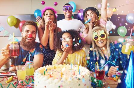 Streamers surrounding group of cheerful friends celebrating a party with large cake and drinks on table in foreground