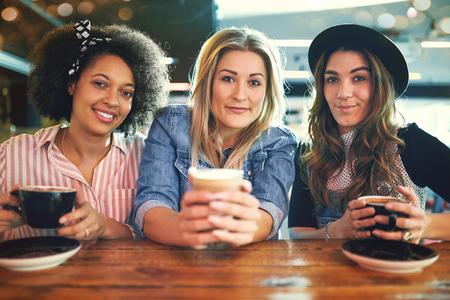 Three attractive multiracial young female students sitting close together at a table in a bistro enjoying hot coffee and smiling at the camera