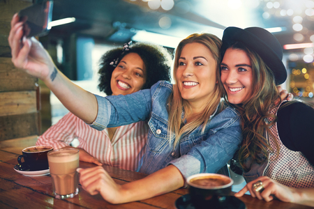 Three attractive girlfriends posing for a selfie together in a cafe as they sit drinking coffee smiling and laughing at the camera on the mobile phone
