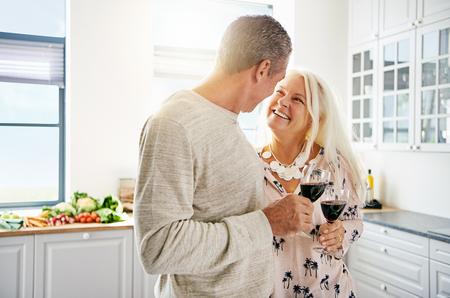 Aanbiddelijk senior koppel drinken wijn in de keuken, samen met de focus op de lachende aantrekkelijke vrouw, die liefdevol naar haar man kijkt