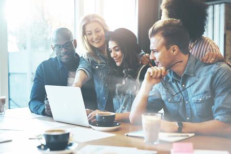 女性の会議テーブルの周りを収集するためのラップトップ コンピューターで何かで同僚を表示 写真素材