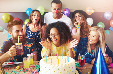 Vivacious attractive young African woman with an afro hairstyle sitting at a table with her friends celebrating and blowing out her birthday candles