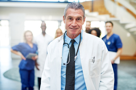 adult doctor with the stethoscope standing in clinic and looking at camera. Reklamní fotografie