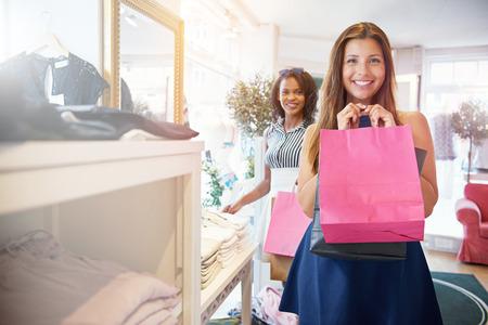 행복 한 미소 아름 다운 젊은 성인 여자 저장소에 친구와 쇼핑하는 동안 빈 핑크색 종이 가방을 들고