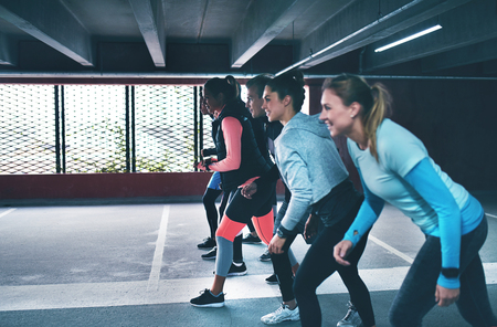 Group of fit young friends working out in a commercial parking lot in town lining up in the starter position for a sprint or race down the interior Imagens
