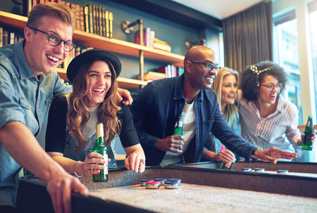 Mixed race friends playing game at bar, laughing and having fun