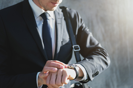 Horizontal crop shot of a manager standing at the gray wall and setting the time on his watch. Stock Photo - 77080128