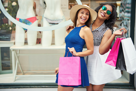 Gorgeous female friends holding shopping bags and posing in front of bikini store window display Stok Fotoğraf