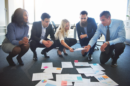 Business team comparing ideas in office, exchanging documents whilst crouched on ground