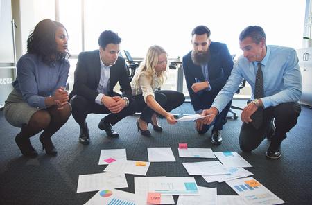 Quipe d'affaires comparant des idées au bureau, échangeant des documents tout en étant accroupie au sol Banque d'images - 77080144