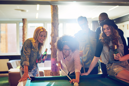 Female pool player taking aim at the cue ball while happy friends with beer bottles stand around watching