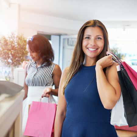 harming: Cute smiling young adult woman in sleeveless blue dress shopping with friend at store. Paper bags in hand. Stock Photo